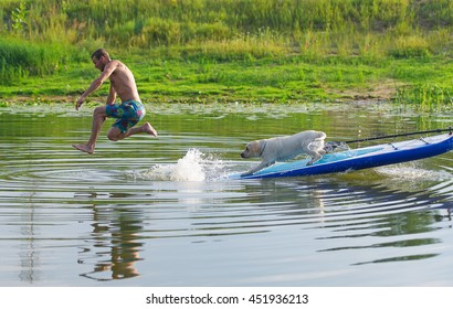 The dog and the man float by the boat on the lake. The man jumps from the boat in water.
