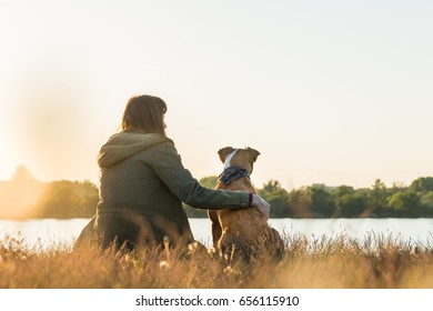 Dog owner and her pet sit at riverbank at sunset. Young female person in parka and puppy hugging and looking in distance near lake at dawn in beautiful autumn landscape
