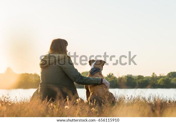 Hundebesitzer und ihr Haustier sitzen bei Sonnenuntergang am Flussufer. Junge weibliche Person in Parka und Welpen umarmt und sieht in der Ferne nahe See bei Morgengrauen in einer schönen Herbstlandschaft