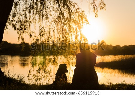 Dog and owner at the lake at sunset. Female person and her pet dog sit together and enjoy beautiful sight under the tree at the river