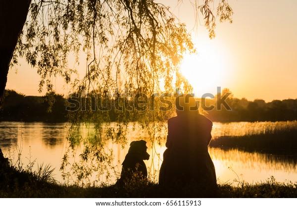 Hund und Besitzer am See bei Sonnenuntergang. Die weibliche Person und ihr Haustier sitzen zusammen und genießen den schönen Blick unter dem Baum am Fluss
