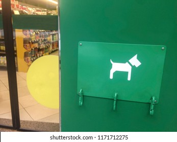 Dog parking bay for pet dogs beside supermarket door. Three free carabiners
