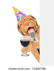 Dog in party hat holding retro microphone and wineglass above white banner. Isolated on white background.