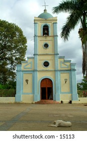 A dog relaxing in front of a church in Vinales, Cuba