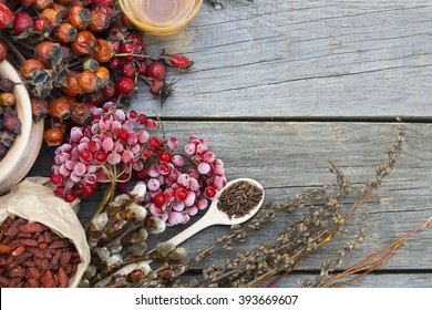 Dog roses and essential oil, bunch of dog rose, Herbal tea, Different types Rosa canina hips and hawthorn, dry goji berries, briar powder in wooden spoon. chinese herbal medicine selection in wooden