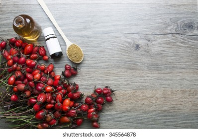 Dog roses and essential oil on wood . bunch of dog rose. Useful drink for health. Herbal tea. Traditional medicine. selective focus
