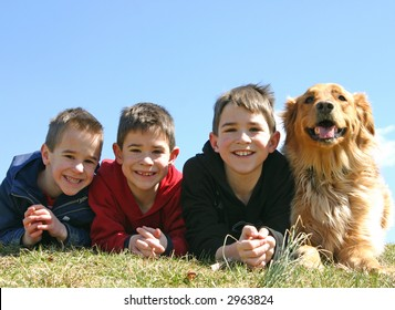 A dog smiling with three young boys