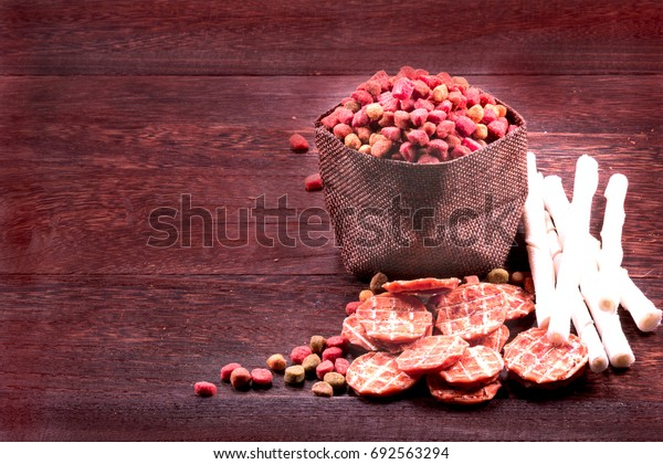 Dog snack ,dog chews, dog biscuits on a grey wooden table wall background with copy space .