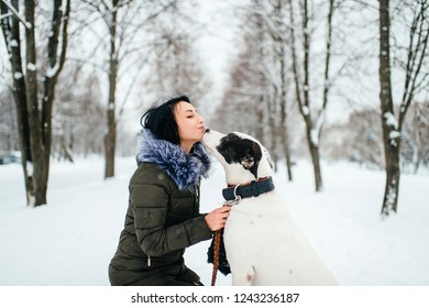 dog sniffs his beautiful young mistress outside on winter day. Young girl on walk with her dog on leash. Beautiful mistress sat down on her knees in front of her dog on winter road