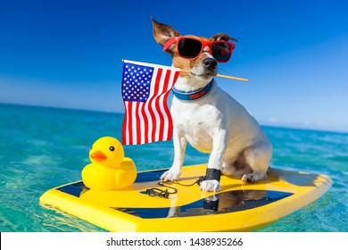 dog surfing on a surfboard wearing sunglasses with a yellow plastic rubber duck, at the ocean shore and usa independence day flag for the 4th of July