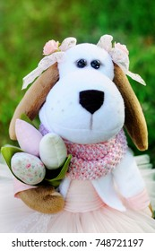 A dog - the symbol of 2018 meets the spring with a bouquet of flowers. doll dog in pink attire with a bouquet of tulips