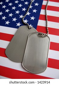 Dog tags and the flag of America. Focused on the dog tags.