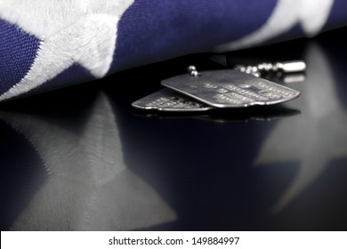 Dog tags or ID tags, once worn by a military veteran with a folded US flag