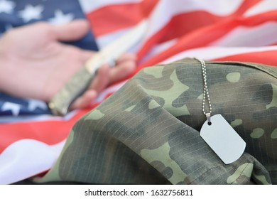 Dog tags lies with hand of man who commit suicide with a knife