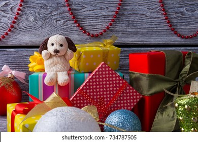 Dog toy and gift boxes. Red beads garland and glass balls, home decorations and presents. Preparing for Xmas party.