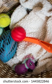 Dog toys, plastic, tennis and foot balls, ball launcher, and a tiny stuffed animal unicorn sit on a fluffy white blanket in a brown wicker basket. The dogs will reach in and grab toys to play with.