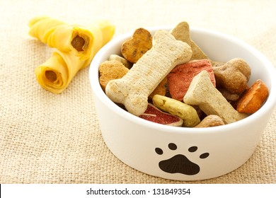 Dog treats in white bowl on burlap cloth