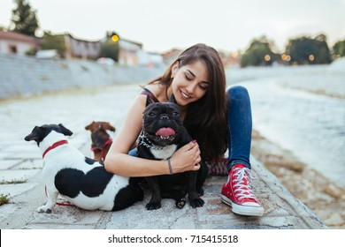 Dog walker with dogs enjoying outdoors next to city river. Selective focus on french bulldog.