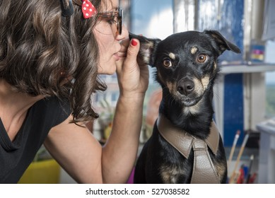 Dog whisperer, puppy gossip; young retro woman whispering things into little cute dog's ear
