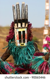 Dogon dancer with mask, representing a deer (antlers), with on the background a so-called tall mask which can be several meters high