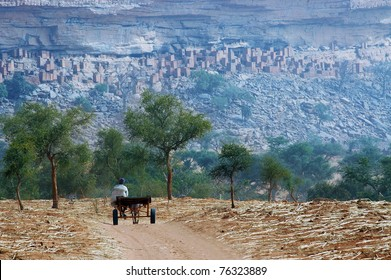 A Dogon man with donkey and cart approaching a village at the base of the Bandiagara escarpment in Mali