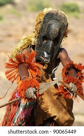 Dogon tribal dancer with mask, bow and spear