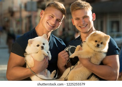 Dogs bring them joy. Muscular men with dog pets. Happy twins with muscular look. Spitz dogs love the company of their family. Happy family on walk. Twins men hold pedigree dogs.