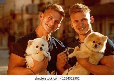 Dogs make life better. Happy twins with muscular look. Spitz dogs love the company of their family. Happy family on walk. Twins men hold pedigree dogs. Muscular men with dog pets.
