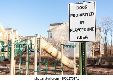 Dogs Prohibited in Playground Area Sign in front of the fences at a fenced playground of a residential suburban neighborhood. Pets may cause disturbance and scare kids during their exercise and play.
