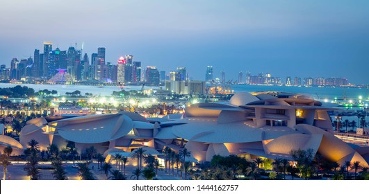 Doha, Doha/Qatar - July 07, 2019 : Qatar National Museum Aerial View  in evening with blue sky and Qatar skyline at back with buildings lights on