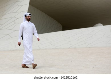 Doha, Qatar - 11 April, 2019: A Qatari man in a long white shirt and a loose headdress walks around The National Museum of Qatar.