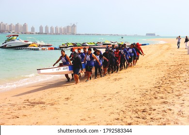 DOHA, QATAR - 11 FEB 2020 : Group of men carrying their ROWBOAT at Katara Beach for a competition during Qatar National Sports Day.