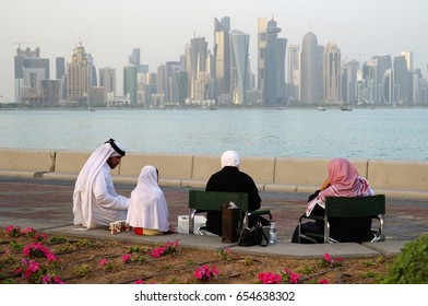DOHA, QATAR -22 DEC 2016- View of a family dressed in traditional Qatari outfits sitting down to admire the view of the modern Doha skyline  on West Bay.