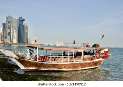 """Doha, Qatar - 28th January 2019: Vintage traditional wooden arab boat """"Dhow"""" with flying national flags of Qatar sways on West bay"""