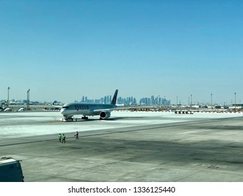 Doha, Qatar - 8th Feb 2019: Qatar airways plane on tarmac of Hamad International Airport, Doha skyline.