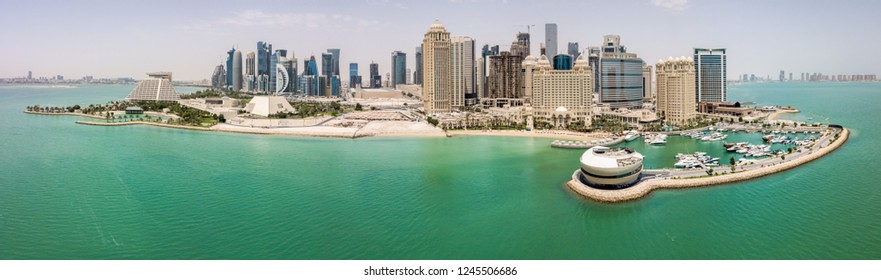 Doha, Qatar - Apr 29 2018: The skyline of Doha. Modern rich middle eastern city of skyscrapers, aerial view, good weather, midday, during hot dry summer, with view of marina and beach of Persian Gulf.