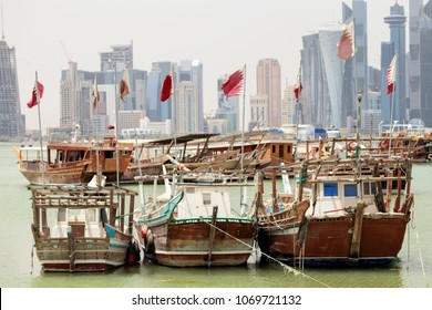 DOHA, QATAR - April 15, 2018: Small fishing boats flying qatari flags in the harbour with towers behind. Shows of loyalty have increased since Qatar was put under economic siege by its Arab neighbours