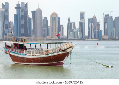 DOHA, QATAR - April 16, 2018:  A traditional dhow anchored  in Doha Bay in front of the city's skyscrapers.