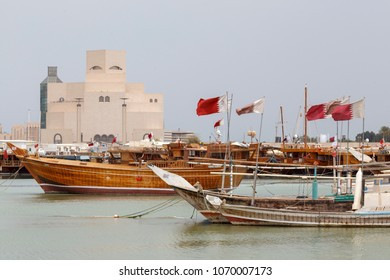 DOHA, QATAR - April 16, 2018: Various traditional wooden boats fly the Qatari flag in front of  the country's landmark Museum of Islamic Art