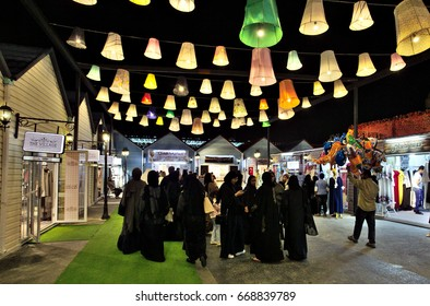 """DOHA, QATAR - APRIL 8, 2017: Qatari women and other visitors in the """"Magical Festival Village"""" beside  Katara heritage area. The village operated in winter and spring."""