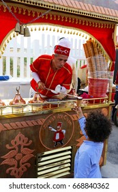 DOHA, QATAR - APRIL 8, 2017: A Turkish traditional ice-cream vendor demonstrates the dramatic process of filling a cone to an enthusiastic  customer at the Magical Festival Village near Katara, Doha.