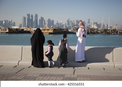 DOHA, QATAR - CIRCA FEBRUARY 2016: Changing times in the fast developing, modern city of Doha, Qatar, as a traditional local family admire the view of West bay from the Corniche.