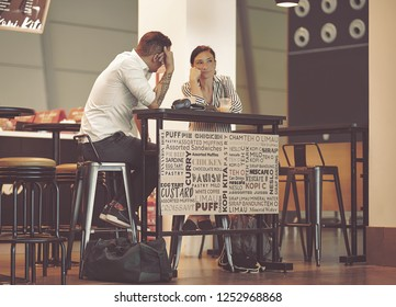 Doha, Qatar - December 9, 2018: beautiful young couple sitting in an airport cafe. Interracial couple talking in coffee shop. Couple sitting at table in cafeteria in Hamad International Airport.