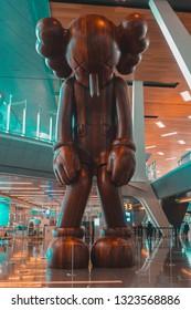 "Doha, Qatar - Feb 16 2019: Wooden sculpture ""Small Lie"" by American pop artist KAWS"