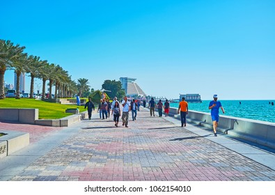 DOHA, QATAR - FEBRUARY 13, 2018: The crowded Al Corniche promenade in West Bay neighborhood with modern building of Sheraton Grand Resort on background, on February 13 in Doha.