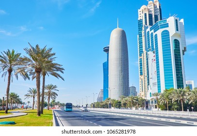 DOHA, QATAR - FEBRUARY 13, 2018: The palms of Sheraton park stretch along the road in Corniche street, separating coastal promenade and skyscrapers of West Bay neighborhood, on February 13 in Doha.