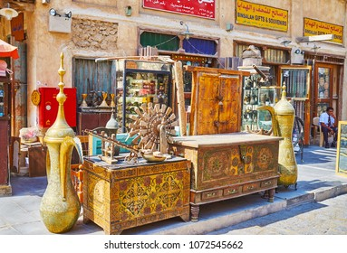DOHA, QATAR - FEBRUARY 13, 2018: Vintage furniture, covered with inlay, rivets, painted patterns and decorative dallah coffee pots in front of the antique store of Souq Waqif, on February 13 in Doha
