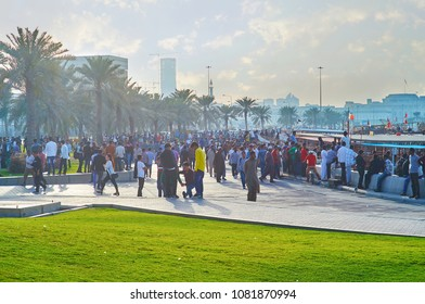 DOHA, QATAR - FEBRUARY 13, 2018: Corniche promenade becomes busy and crowded place in the evening, multitude of male migrant workers like to spend free time here with friends, on February 13 in Doha
