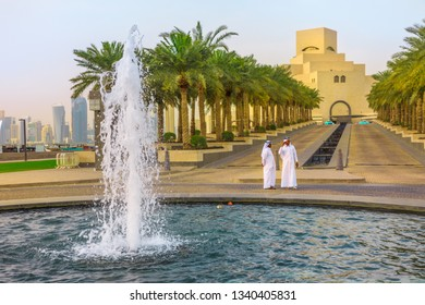 Doha, Qatar - February 16, 2019: two Arabs standing near fountain of Museum of Islamic Art with skyscrapers of West Bay skyline on background. Middle East, Arabian Peninsula, Persian Gulf.