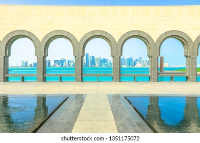 Doha, Qatar - February 16, 2019: series of arches reflections in a pool fountain inside Museum of Islamic Art. Popular tourist seafront. Middle East, Persian Gulf. Doha West Bay skyline on background.